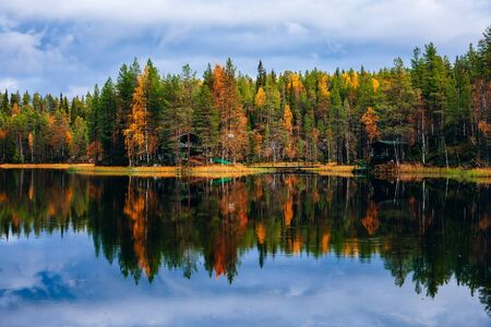 Autumn landscape. Fall colors reflection in blue lake in Finland