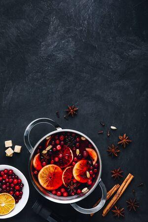 Boisson chaude au vin chaud avec canneberges, oranges, pommes et épices sur fond de béton foncé. Vue de dessus, espace de copie