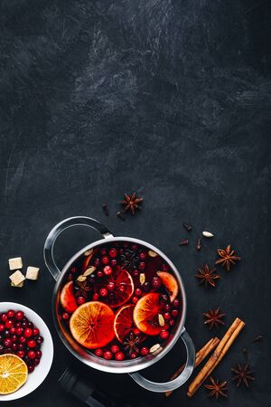 Mulled Wine Hot Drink with Cranberries, oranges, apples and spices on dark concrete background. Top view, copy space