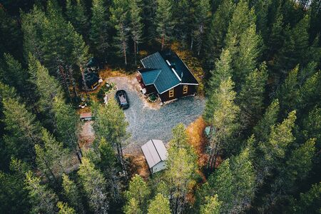Aerial view of secluded cottage in the woods. Log cabin in the forest in rural Finland. View from above.