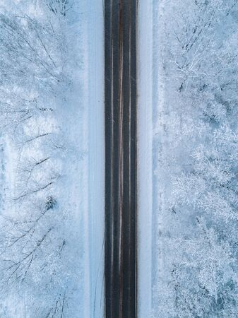 Aerial view of a winter road with snow covered forest