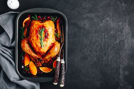Thanksgiving baked chicken or turkey with spices, oranges and cranberries on dark concrete stone background. 版權商用圖片