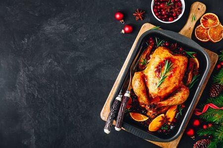 Christmas baked chicken or turkey with spices, oranges and cranberries on dark concrete stone background.