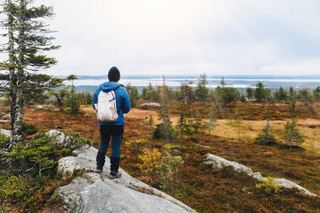 Man traveler in a blue jacket with a backpack hiking in the autumn forest in Lapland Finland.