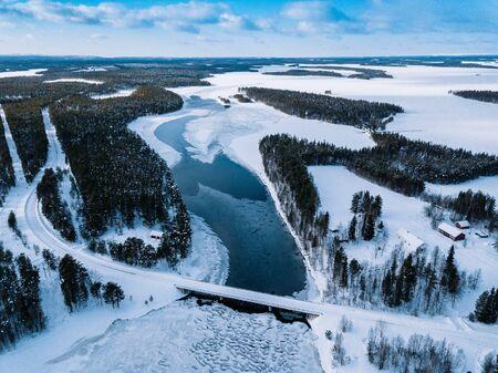 Aerial top view of bridge road above frozen river in snow winter Finland Lapland.