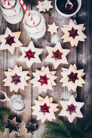 Traditional Linzer Christmas cookies filled with raspberry jam on wooden background.