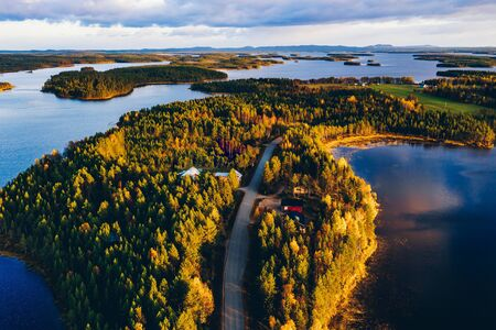 Aerial view of road through autumn forest with blue lakes in Finland Lapland.