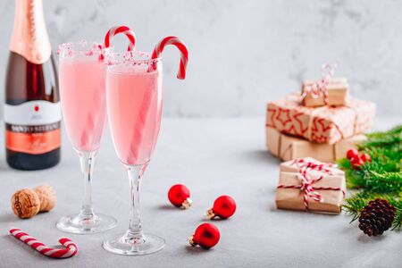Festive Christmas drink Peppermint Bark Mimosa cocktail with champagne or prosecco and candy cane on gray stone concrete background, copy space. Stok Fotoğraf - 133847591