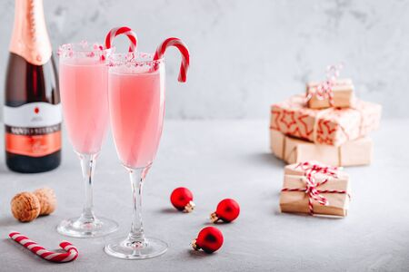 Festive Christmas drink Peppermint Bark Mimosa cocktail with champagne or prosecco and candy cane on gray stone concrete background, copy space. Stok Fotoğraf