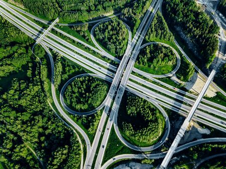 Aerial top view of Highway road and overpass with green forests on a summer day in Finland.