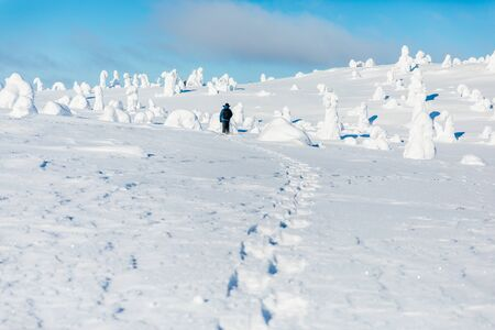 Man hiking in the mountains on snowshoes in snow winter Finland Lapland.