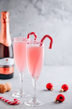 Festive Christmas drink Peppermint Bark Mimosa cocktail with champagne or prosecco and candy cane on gray stone concrete background, copy space. Stok Fotoğraf - 133847616