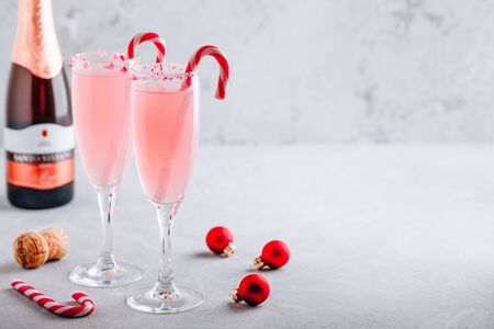 Festive Christmas drink Peppermint Bark Mimosa cocktail with champagne or prosecco and candy cane on gray stone concrete background, copy space. Reklamní fotografie