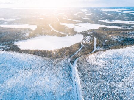 Aerial top view of snow winter mountain landscape with forests, frozen lakes and road in Finland Lapland. Reklamní fotografie