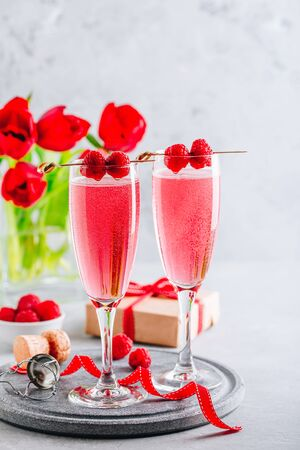 Pink cocktail with champagne or prosecco and fresh raspberries for St. Valentine's day.