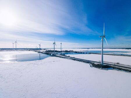 Aerial view of windmills with blue frozen river in snow winter Finland. Wind turbines for electric power with clean and Renewable Energy