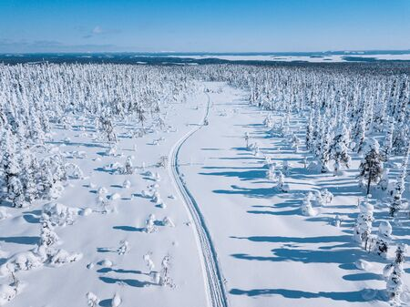 Aerial view of white winter forest with snow covered trees and rural road in Finland, Lapland Standard-Bild