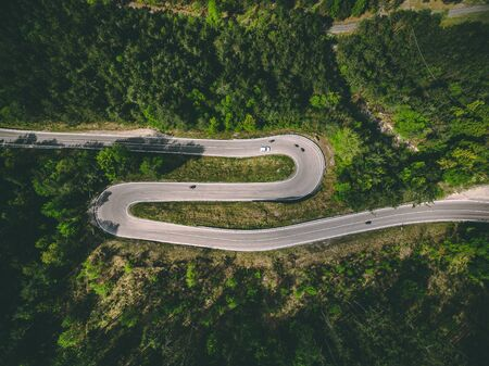Aerial view of winding country road with cars and motorcycles in Italy