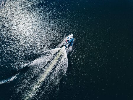 Aerial view of speed Boat or yacht at deep blue sea or lake leaving a wake