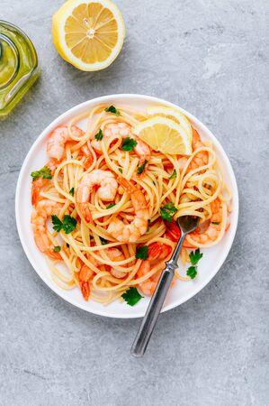 Spaghetti de pâtes aux fruits de mer aux crevettes et au persil sur fond de pierre grise. Vue de dessus, espace de copie