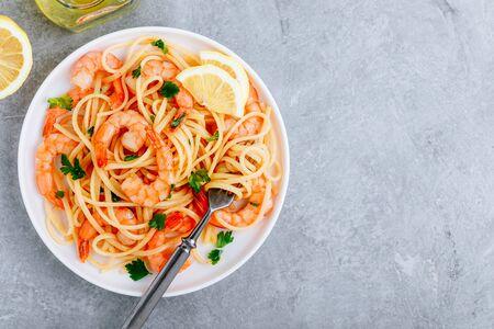 Spaghetti de pâtes aux fruits de mer aux crevettes et au persil sur fond de pierre grise. Vue de dessus, espace de copie Banque d'images