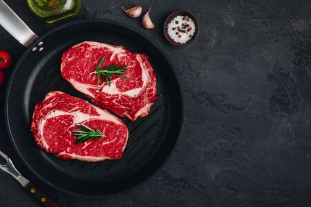 Ribeye Steak, Raw fresh beef meat with salt and rosemary in grill pan on dark stone background