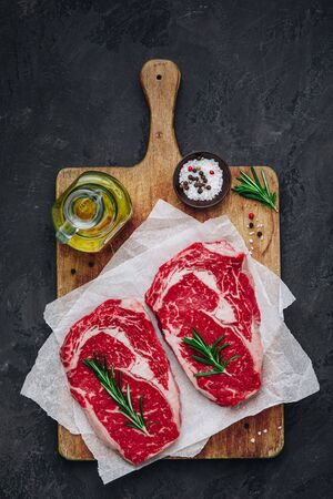 Ribeye Steak, Raw fresh beef meat with salt and rosemary ready for barbecue on dark stone background 스톡 콘텐츠