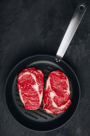 Ribeye Steak, Raw fresh beef meat in grill pan on dark stone background