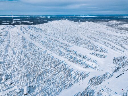 Aerial view of snow covered forest and ski resort slope in winter Finland Lapland. Drone photography from above Stock Photo