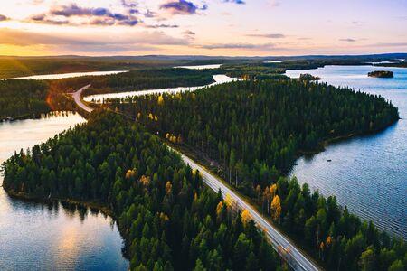Luftaufnahme der Landstraße im grünen Sommerwald mit blauen Seen bei Sonnenuntergang in Finnland