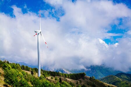 Aerial view of wind turbine farm. Wind power plants in green summer landscape with clouds in Italy.