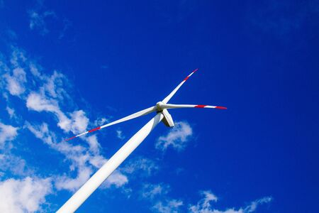 Aerial view of wind turbine closeup. Wind power plants in blue sky with clouds in Italy.