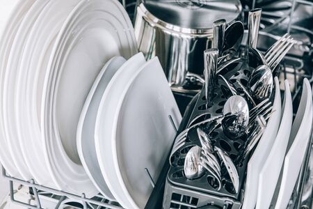 Open dishwasher with clean dishes close-up after washing. Clean utensil in open dishwashing machine. Foto de archivo