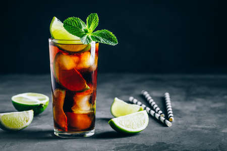 Rum and  Cuba Libre ice cold drink cocktail with lime and mint on dark background.