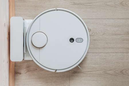 Wireless robot vacuum cleaner return to charging at dock in clean wooden floor. Smart household technologies.