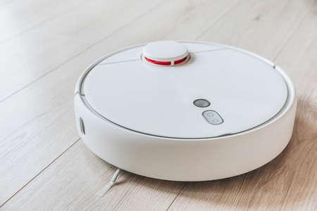 Wireless robot vacuum cleaner working on wooden floor. Smart household technologies.
