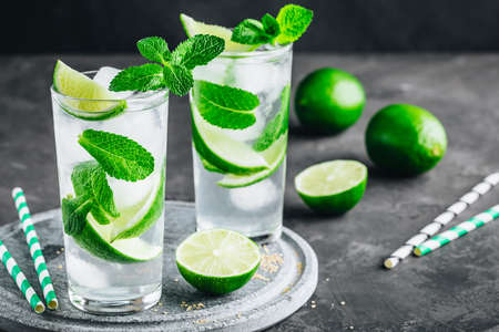 Mojito cocktail with ice, fresh mint and lime in glass on dark stone background. Refreshing ice cold summer drink.