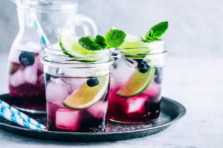 Blueberry Mojito with lime and fresh mint. Iced cold summer drinks in glass jar.