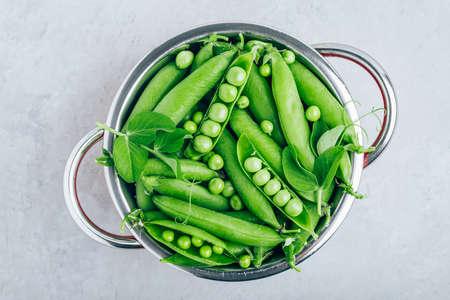Organic Fresh Raw Green Peas in a colander on gray stone background, top view Standard-Bild