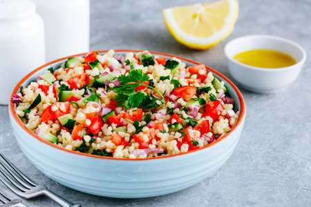 Couscous Tabbouleh Salad with fresh tomatoes, cucumbers and red onions in bowl on gray stone background