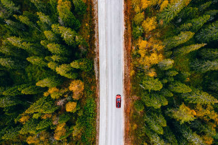 Aerial view of rural road with red car in yellow and orange autumn forest in rural Finland. Standard-Bild