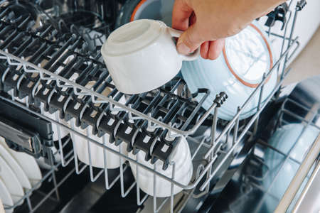 Dishwasher machine close-up. Woman hand taking out clean dish after washing.