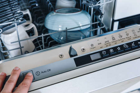 Run the dishwasher machine. Close-up of woman's finger pressing start button on dishwasher in the kitchen.
