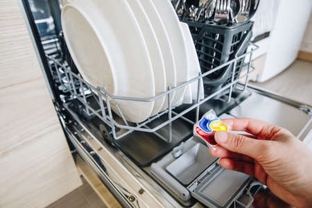 Woman hand putting tablet in dishwasher detergent box. Dishwasher machine full loaded close-up.