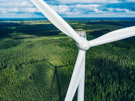 Aerial view of windmill close-up in green summer forest in Finland. Wind turbines for electric power with clean and Renewable Energy