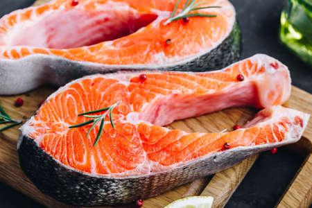 Fresh raw Salmon Steaks prepared for cooking on dark stone background. Stock Photo