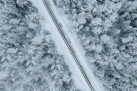 Aerial view of road with car in winter forest covered with snow.