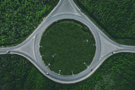 Aerial view of a traffic roundabout and road junctions in green summer forest