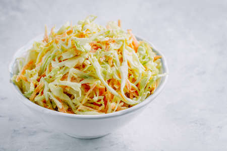 Traditional coleslaw salad with fresh sliced carrots and cabbage in a white bowl with copy space