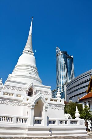 Pagoda in famous temple located in the center of Bangkok business area versus modern shopping building